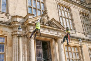 Abseiling stonemasons James Preston and Columba Strachey inspecting the coat of arms at Longleat House